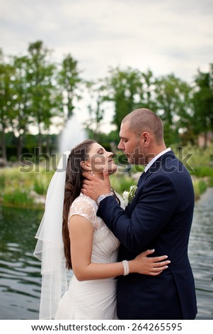 Groom gently hugs bride outdoors in the countryside.The bride and groom in the garden. Beautiful couple in love.