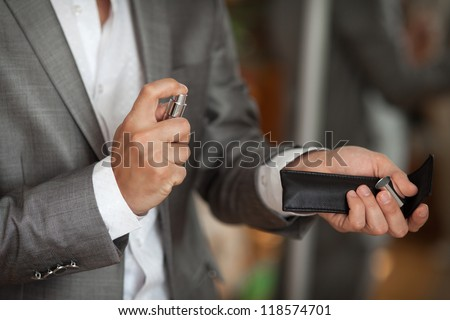 groom have a final preparation for wedding - man holing a parfume bottle and spraying fragrance on hand. Wedding day moment and bridal concept. series in my portfolio - stock photo