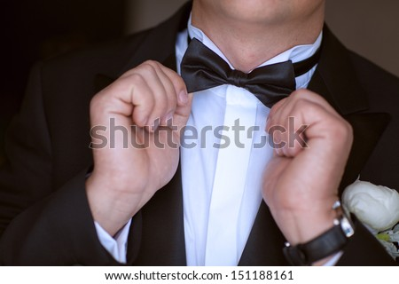 groom have final preparation for wedding. man with wedding Boutonniere On Jacket. Wedding day moment and bridal concept. Handsome groom at wedding tuxedo. Stylish bridal decoration on suit. marriage. - stock photo