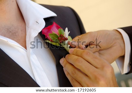 Groom having  boutonniere pinned on.