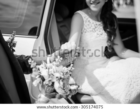 Groom helping his bride out of the wedding car. Selective focus on hands - stock photo