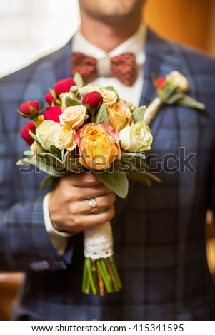 Groom hold wedding bouquet in his hand. Close-up - stock photo