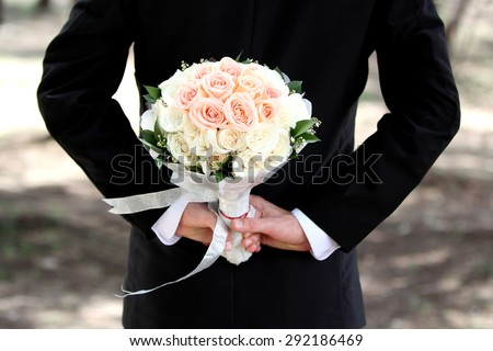 groom holding a bouquet behind his back - stock photo