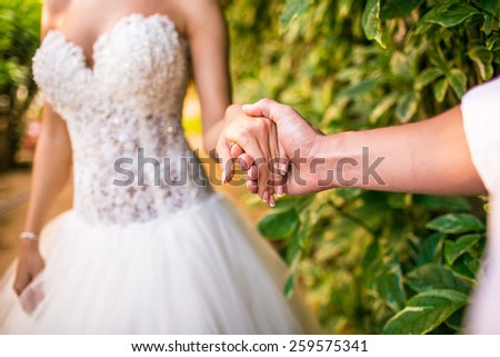groom holding a brides hand outdoor - stock photo