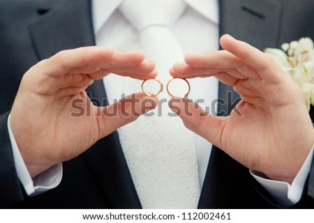 groom holding a gold rings - stock photo