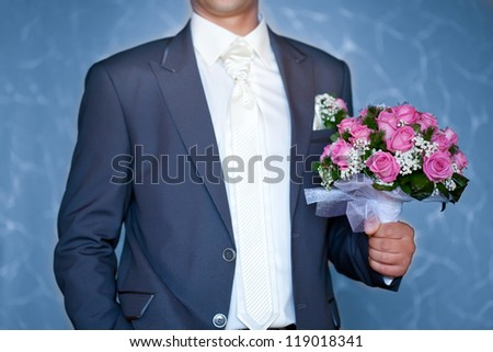 groom holding beautiful  flowers bouquet
