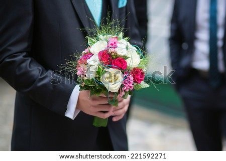 Groom holding beautiful wedding bouquet of his bride in his hands