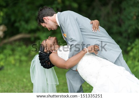 Groom holding bride in dance pose on wedding day - stock photo