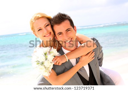 Groom holding bride on his back - stock photo