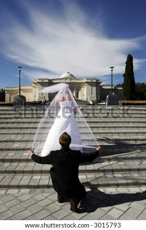 Groom holding brides veil while kneeling from behind - stock photo