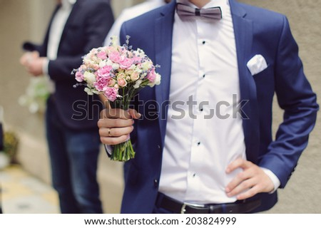 groom holding elegant wedding bouquet - stock photo