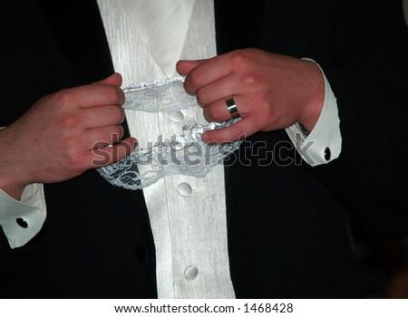 groom holding garter at wedding - stock photo