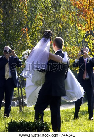 Groom holding his bride for a wedding photography - stock photo
