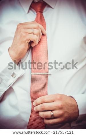 Groom holding his tie - stock photo