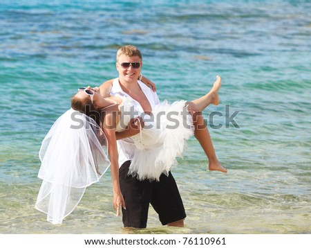 Groom holding up a bride on the tropical beach - stock photo