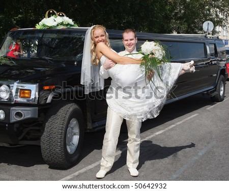 Groom holds  bride on hands near a long wedding  limousine