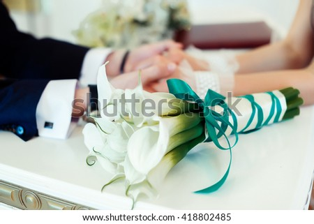 groom holds his bride's hands, bouquet of callas - stock photo