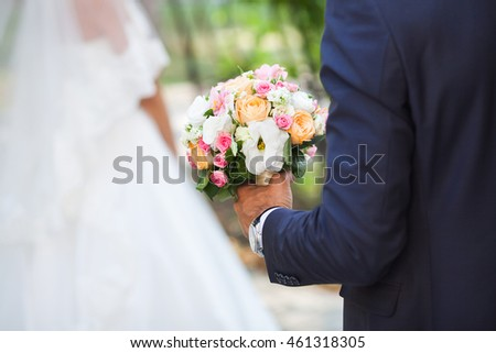 Groom holds the wedding bouquet of flowers