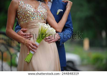 groom hugging woman at a wedding bouquet of white calla lilies. - stock photo