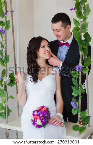 Groom hugs bride sitting on a swing with the vine - stock photo
