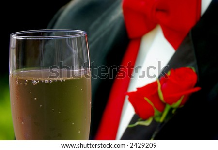 Groom in a tux holding a glass of champagne - stock photo