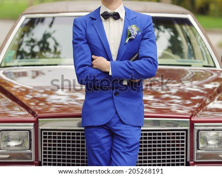 groom in blue suit standing at car - stock photo