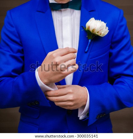 Groom in blue suit with bouquet before wedding ceremony - stock photo
