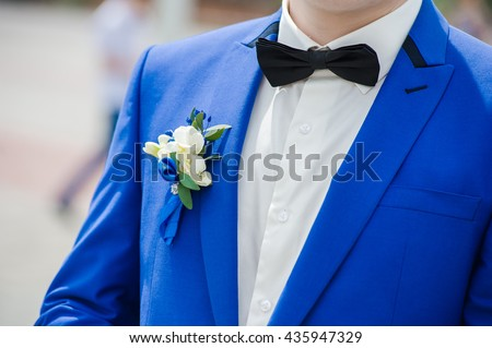 Groom in blue suit with wedding bouquet - stock photo