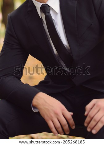 groom in elegant suit in park - stock photo