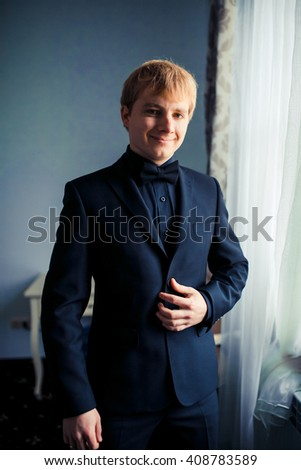 Groom in the morning on the wedding day buttoning cuffs his hands on his suit - stock photo