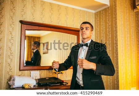 Groom in the morning on the wedding day buttoning cuffs his hands on his suit