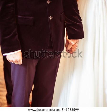 Groom in velvet jacket holds bride's hand