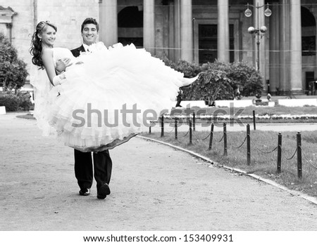 groom is carrying bride on arms on city park road - stock photo