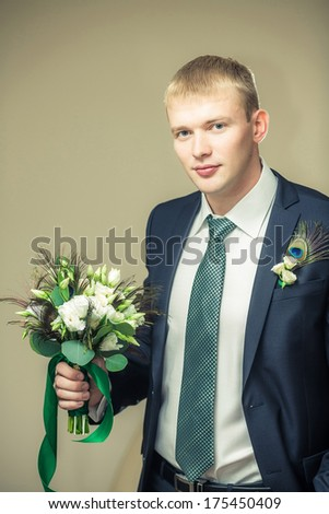 Groom is holding a flower's bouquet and looking in the camera. - stock photo