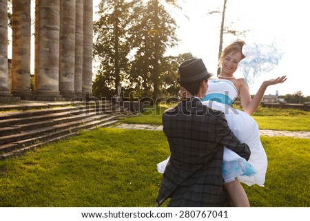 groom is holding his smiling bride on the background grass, columns and stairs - stock photo