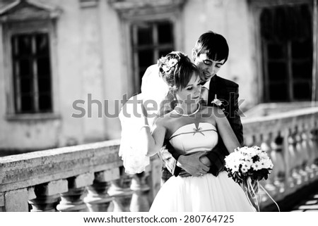 groom is hugging his wife on background old castle - stock photo
