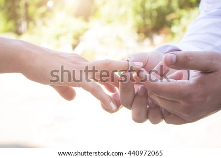 Groom is putting a ring on finger of his bride. Wedding concept. Happy newlyweds. - stock photo