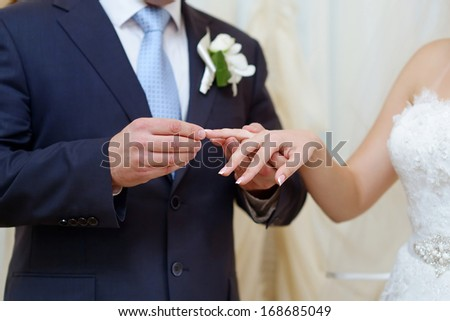 Groom is putting the wedding ring on bride's finger - stock photo