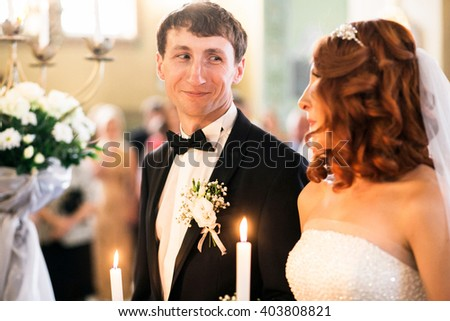 Groom is smiling to his bride in the church