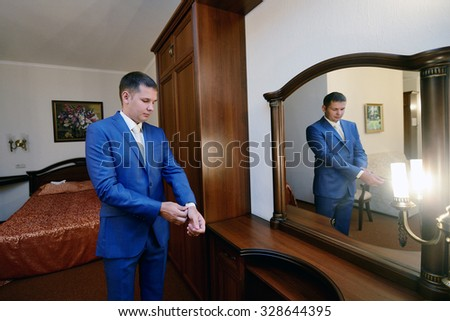 Groom is wearing a suit indoors. Male portrait of handsome guy. Beautiful model boy in colorful wedding clothes. Man is posing - stock photo