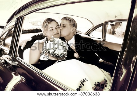 Groom kisses Bride on the backseat of a car - stock photo