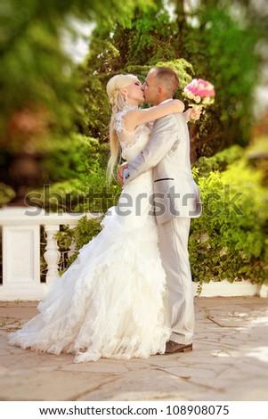Groom kissing bride on their wedding walk - stock photo