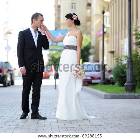 Groom kissing bride's hand outdoors in the street - stock photo