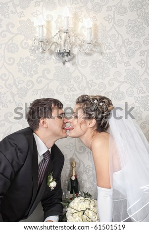 Groom kissing bride with a long tongue in stylish indoors