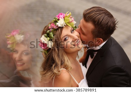 groom kissing his bride in the city - stock photo