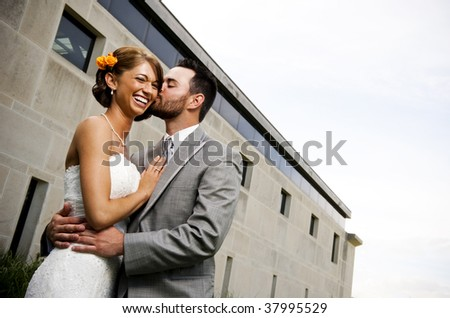 Groom kissing his new bride - stock photo