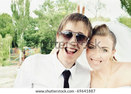 Groom laughing in sunglasses and bride showing tongue and doing rabbit ears - stock photo