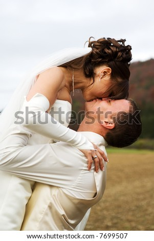 Groom lifted his bride - they are kissing each other with a smile. - stock photo