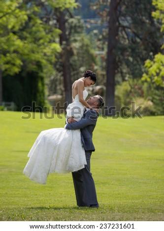 Groom lifting bride in outdoor garden setting - stock photo