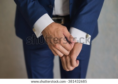 groom, man correct sleeves on shirt, hands close-up, dressing, man's style,  - stock photo